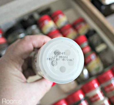 Person examining the expiration date on a spice bottle.