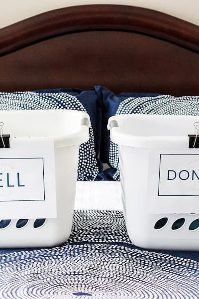 "laundry baskets on a bed labeled ""sell"" and ""donate""."