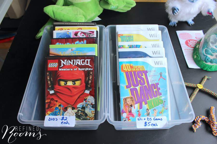 DVDs and Wii games with price tags displayed on a table at a garage sale.