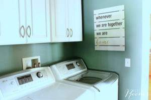teal colored laundry room with white appliances.