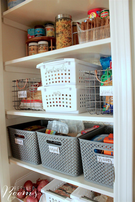an organized pantry full of labeled baskets and containers.