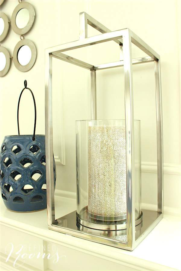 Contemporary lanterns decorate the mantle in our great room makeover