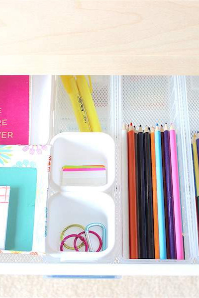 desk drawer filled with colorful office supplies organized with drawer dividers.
