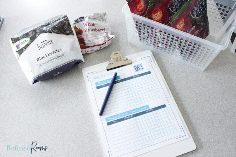 kitchen countertop with printable freezer inventory on clipboard next to freezer items