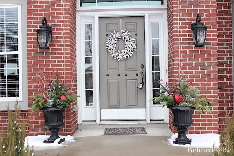 front entryway of home for sale in winter with tasteful winter decorations.