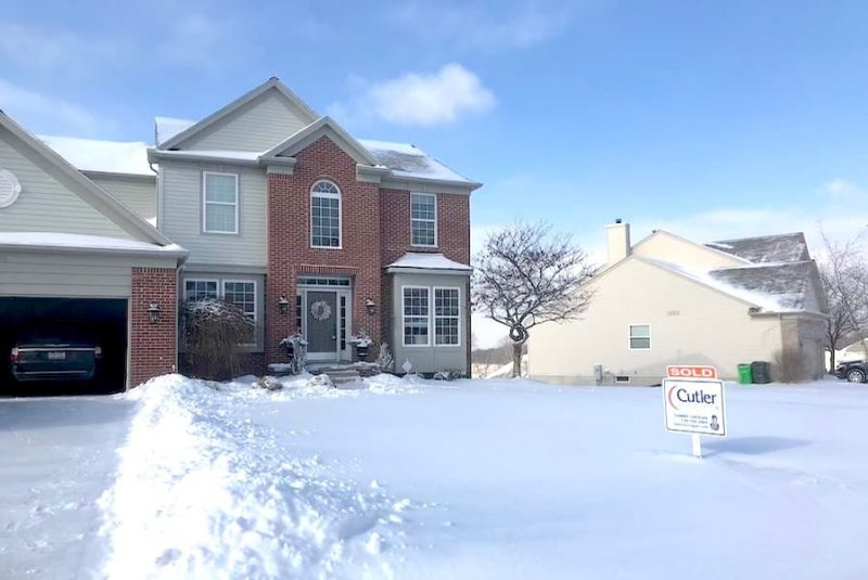 house with snow in front yard and SOLD real estate sign.